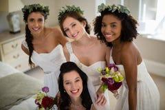 Portret van glimlachend bruid en bruidsmeisje in woonkamer stock foto