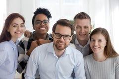 Portret van glimlachend divers millennial team die samen stellen stock foto