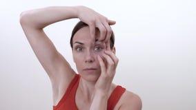 Portret van glimlachend donkerbruin meisje die oefening doen om rimpels in de hoeken van de ogen van de hand te doen stock video