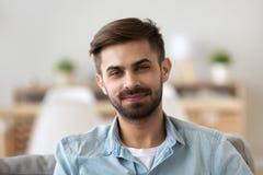 Portret van glimlachend mannetje die camerazitting thuis bekijken royalty-vrije stock foto