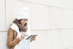 Portret van glimlachend meisje met bonnet die tabletcomputer op wa met behulp van royalty-vrije stock foto