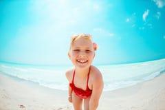 Portret van glimlachend modern kind in rode strandkleding op zeekust royalty-vrije stock afbeeldingen