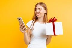 Portret van glimlachende aantrekkelijke vrouw, houdend giftdoos, zich bevindt en gebruikend mobiele die telefoon, op gele achterg stock afbeelding