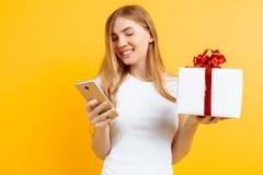 Portret van glimlachende aantrekkelijke vrouw, houdend giftdoos, zich bevindt en gebruikend mobiele die telefoon, op gele achterg royalty-vrije stock foto