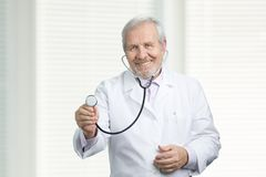 Portret van glimlachende arts die stethoscoop met behulp van royalty-vrije stock afbeelding