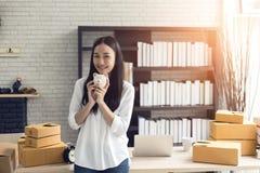 Portret van glimlachende Aziatische jonge vrouw met de dozen die van het spaarvarken en van het karton zich binnenshuis bevinden royalty-vrije stock foto