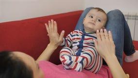 Portret van glimlachende baby op moeder` s overlapping op bank stock videobeelden