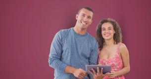 Portret van glimlachende bedrijfsmensen met digitale tablet tegen roze achtergrond Royalty-vrije Stock Foto's