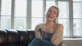 Portret van glimlachende blonde Een mooie jonge vrouw bekijkt de camera en lacht Toont zijn duim en helt zijn hoofd over stock videobeelden