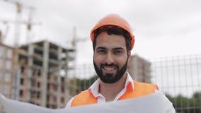 Portret van glimlachende bouwvakker in oranje helm die de camera bekijken De bouwer met bouwproject stock footage