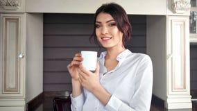 Portret van glimlachende elegante huisvrouwenvrouw die van onderbreking genieten die witte mok houden bekijkend camera stock video