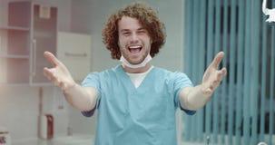 Portret van glimlachende gelukkige arts die met krullend haar en perfecte tanden u uitnodigen aan het bezoeken van zijn kliniek,  stock video