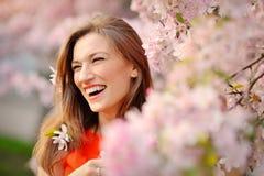 Portret van glimlachende gezichts Mooie donkerbruine vrouw op de achtergrond van de lentebomen Royalty-vrije Stock Fotografie