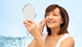 Portret van glimlachende hogere vrouw met spiegel royalty-vrije stock afbeelding