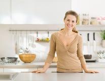 Portret van glimlachende huisvrouw in moderne keuken stock afbeeldingen