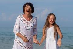 Portret van glimlachende jonge kleindochter en bejaarde grootmoeder royalty-vrije stock foto