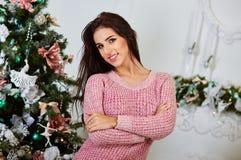 Portret van glimlachende jonge vrouw dichtbij Kerstmis Stock Foto