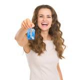 Portret van glimlachende jonge vrouw die huissleutel tonen Royalty-vrije Stock Foto's