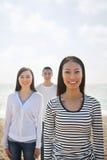 Portret van Glimlachende Jonge Vrouw en Vrienden bij het Strand Stock Afbeeldingen