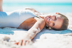 Portret van glimlachende jonge vrouw in zwempak die op strand zonnebaden Stock Afbeelding