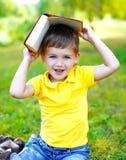 Portret van glimlachende kindjongen met boek op het gras in de zomer Stock Fotografie