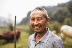 Portret van glimlachende landbouwer met vee op de achtergrond, landelijk China, Shanxi-Provincie Stock Foto