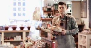 Portret van glimlachende mannelijke eigenaar van delicatessenwinkel stock videobeelden