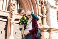 portret van glimlachende mens het verrassen vrouw met boeket van bloemen stock foto