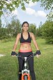 Portret van glimlachende mooie vrouw die oefening met fiets doen stock foto