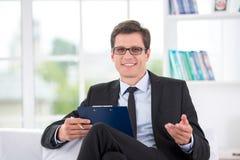 Portret van glimlachende psycholoog in bureau Stock Foto