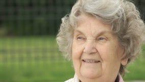 Portret van glimlachende rijpe oude vrouw in openlucht stock videobeelden