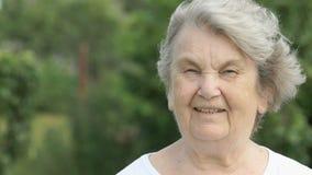 Portret van glimlachende rijpe oude vrouw in openlucht stock footage