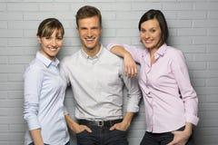 Portret van 3 glimlachende studenten, dat over een grijze bakstenen muur wordt geïsoleerd stock afbeelding