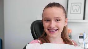 Portret van glimlachende tiener met steunen in het bureau van de tandarts stock videobeelden