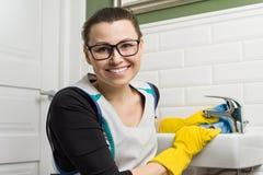 Portret van glimlachende volwassen vrouw in glazen, rubberhandschoenen die huis het schoonmaken, vrouwelijke schoonmakende badkam stock afbeeldingen