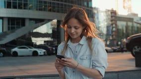 Portret van glimlachende vrouw die de erkenning van de smartphonestem gebruiken Jong Kaukasisch meisje die met oortelefoons en he stock videobeelden