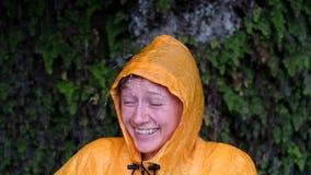 Portret van glimlachende vrouw in een gele regenjas in de stortbui, langzame motie stock video