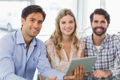 Portret van glimlachende vrouw en twee mannen die digitale tablet gebruiken Royalty-vrije Stock Afbeeldingen