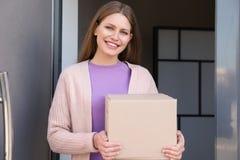 Portret van glimlachende vrouw met pakket bij deur De dienst van de levering royalty-vrije stock afbeelding