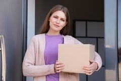 Portret van glimlachende vrouw met pakket bij deur De dienst van de levering royalty-vrije stock afbeeldingen