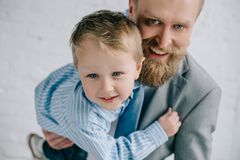 portret van glimlachende zakenman in kostuum en weinig zoon het koesteren stock afbeelding