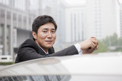 Portret van Glimlachende Zakenman Leaning On Car stock afbeelding