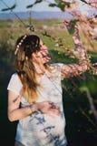 Portret van glimlachende zwangere vrouw in de aard, de lente Royalty-vrije Stock Afbeeldingen