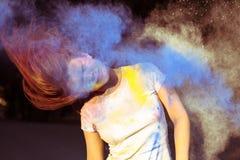 Portret van glorierijke vrouw met blazend droog kleuren binnen poeder Holi Stock Afbeelding