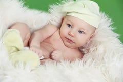 Portret van grappige babyjongen die op bont wit bed rusten Stock Foto's