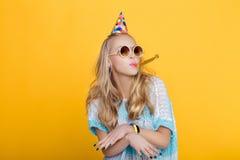 Portret van grappige blonde vrouw in verjaardagshoed en blauw overhemd op gele achtergrond Viering en partij stock foto