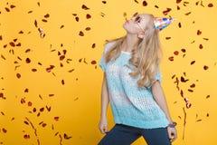 Portret van grappige blonde vrouw in verjaardagshoed en rode confettien op gele achtergrond Viering en partij stock foto's