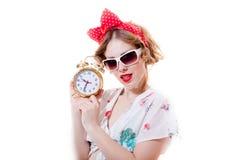 Portret van grappige jonge blonde mooie dame die met wekker met glazen camera bekijken Stock Afbeelding