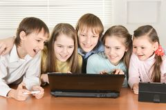 Portret van grappige jongens en meisjes die digitale apparaten met behulp van samen bij de lijst thuis stock afbeeldingen