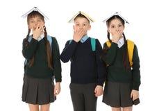 Portret van grappige kinderen in school eenvormig met boeken op hoofden royalty-vrije stock afbeelding